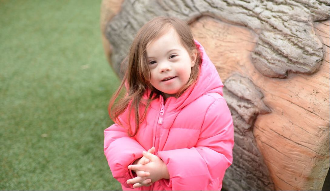 Photo of Onna wearing a bright pink coat outside next to a tree
